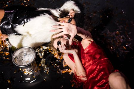 Foto de Overhead view of blonde girl in red dress gesturing while smiling and lying on floor with confetti near african american friend on black - Imagen libre de derechos