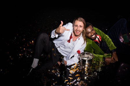 Photo for Happy and drunk man showing middle finger while sitting near african american man and confetti of black - Royalty Free Image