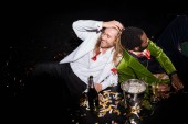 "Постер, картина, фотообои ""happy and drunk multicultural men lying near shiny confetti of black """