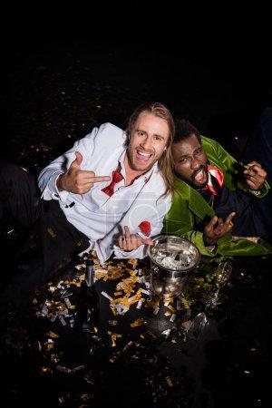 Photo pour Happy and drunk multicultural men showing middle fingers while lying near confetti of black - image libre de droit