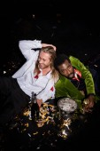 """Постер, картина, фотообои """"happy man smiling with closed eyes and sitting near drunk african american man and confetti of black """""""