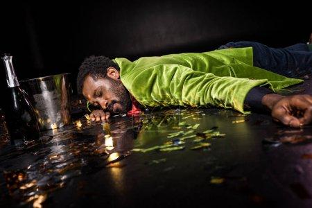 Foto de Selective focus of drunk african american man lying on floor with confetti near ice bucket and bottle of champagne on black - Imagen libre de derechos