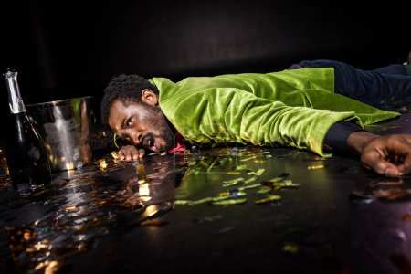 Photo for Selective focus of drunk african american man lying on floor with shiny confetti near ice bucket and bottle of champagne on black - Royalty Free Image