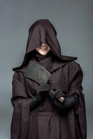 Photo pour Femme de sourire dans le costume de mort retenant le couperet d'isolement sur le gris - image libre de droit