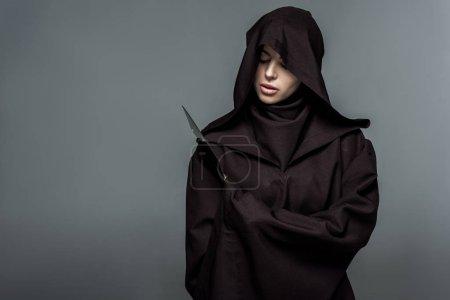 Photo pour Femme en costume mortel tenant un couteau isolé sur gris - image libre de droit