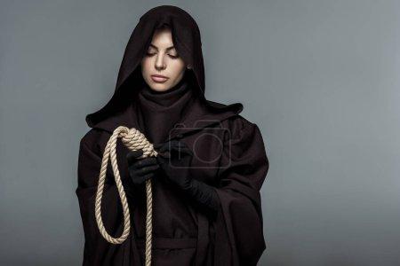 Photo pour Femme en costume de mort tenant noeud suspendu isolé sur gris - image libre de droit
