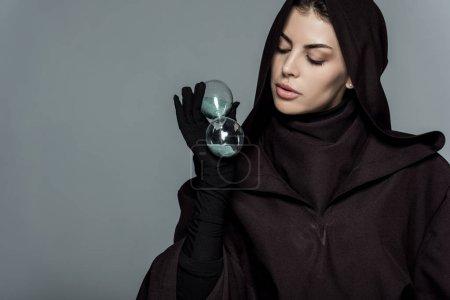 Photo pour Femme en costume de mort tenant du verre de sable isolé sur gris - image libre de droit