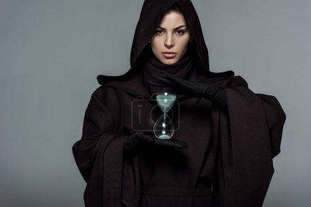 Photo pour Vue de face de la femme en costume de mort tenant horloge de sable isolé sur gris - image libre de droit