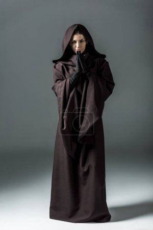 Photo for Full length view of smiling woman in death costume showing please gesture on grey - Royalty Free Image