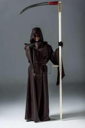 Photo for Full length view of woman in death costume holding scythe and pointing with finger on grey - Royalty Free Image