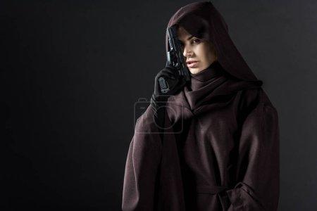Photo pour Femme en costume de mort tenant une arme isolée sur un noir - image libre de droit