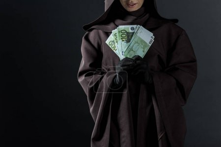 Photo for Cropped view of woman in death costume holding euro banknotes isolated on black - Royalty Free Image