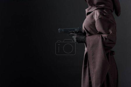 Photo pour Vue partielle de femme dans le pistolet de fixation de costume de mort sur le noir - image libre de droit