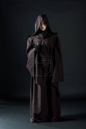 Photo for Full length view of woman in death costume aiming gun at camera on black - Royalty Free Image
