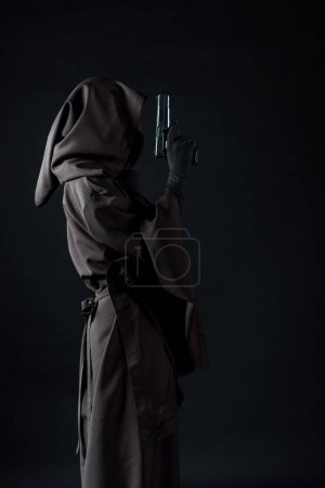 Photo for Side view of woman in death costume holding gun isolated on black - Royalty Free Image