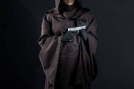 Photo for Cropped view of woman in death costume holding gun on black - Royalty Free Image
