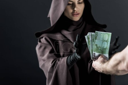 Photo for Partial view of man giving euro banknotes to woman in death costume isolated on black - Royalty Free Image