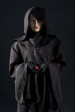 woman in death costume holding dice isolated on black