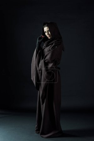 full length view of woman in death costume holding dice on black