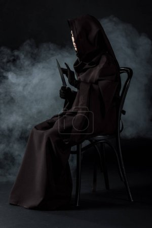 Photo for Woman in death costume holding knife and sitting on chair on black - Royalty Free Image