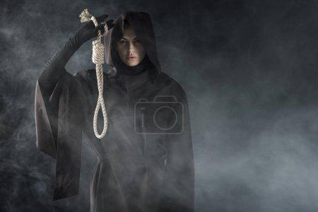 Photo pour Vue avant de la femme dans le costume de mort retenant l'étau suspendu dans la fumée sur le noir - image libre de droit