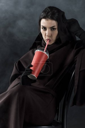 Photo for Woman in death costume sitting on chair and drinking beverage on black - Royalty Free Image