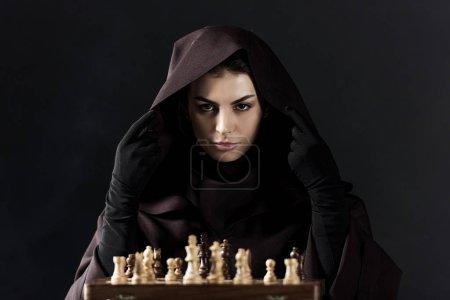 Photo pour Vue avant de la femme dans le costume de mort avec des échecs d'isolement sur le noir - image libre de droit