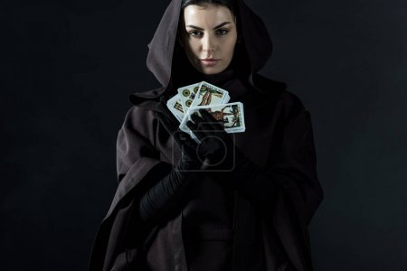 Photo pour KYIV, UKRAINE - APRIL 18, 2019: front view of woman in death costume holding tarot cards isolated on black - image libre de droit