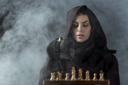 Photo pour Woman in death costume playing chess in smoke on black - image libre de droit