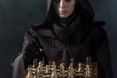 Photo pour Cropped view of woman in death costume playing chess on black - image libre de droit