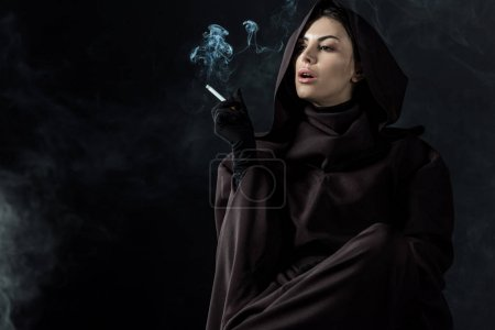 Photo pour Woman in death costume smoking cigarette on black - image libre de droit