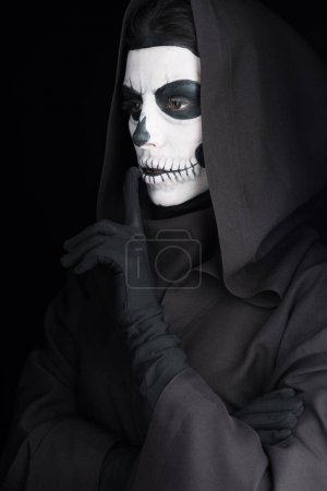 Photo pour Woman with skull makeup showing hush sign isolated on black - image libre de droit
