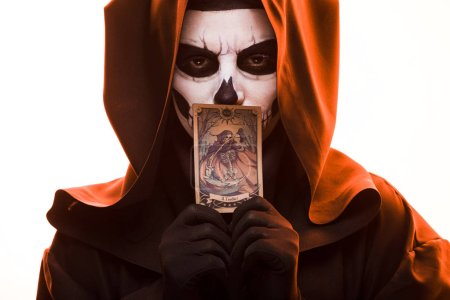 Foto de KYIV, UKRAINE - APRIL 18, 2019: woman with skull makeup holding tarot card isolated on white - Imagen libre de derechos
