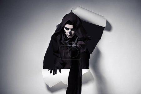 Photo pour Femme en costume de mort tissu tendu la main sortant du trou dans le papier - image libre de droit