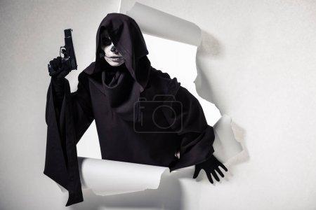 Photo pour Femme en costume de mort tenant une arme et sortant du trou dans le papier - image libre de droit