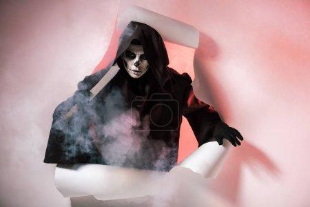 Photo pour Femme en costume de mort tenant le cordonnier et sortant du trou dans le papier - image libre de droit