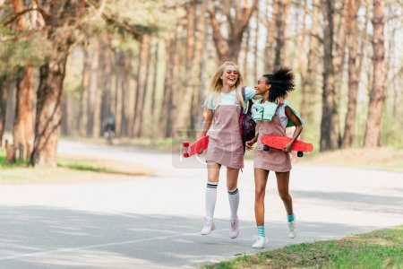 Photo for Full length view of laughing multiethnic friends with penny boards jumping on road - Royalty Free Image