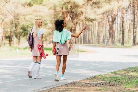 Foto de Vista trasera de dos amigos multiculturales con tablas de centavos caminando por carretera - Imagen libre de derechos