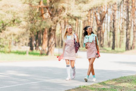 Photo for Full length view of two smiling multicultural friends holding penny boards and walking on road - Royalty Free Image