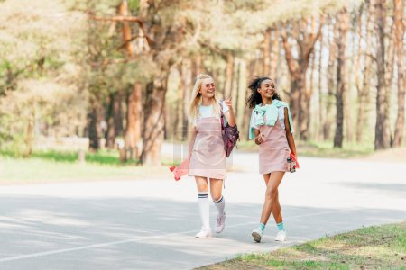 full length view of two smiling multicultural friends holding penny boards and walking on road
