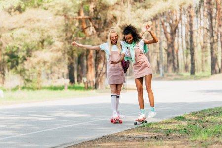 Photo pour Vue pleine longueur de deux amis multiculturels souriants faisant du skateboard sur des planches de penny sur la route - image libre de droit