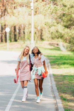 Foto de Vista de longitud completa de dos amigos multiculturales con tablas de centavos abrazando mientras camina por la carretera - Imagen libre de derechos