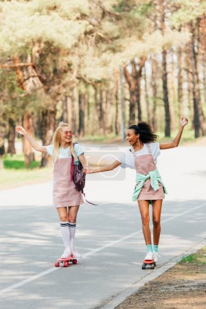 Photo for Full length view of two smiling multicultural friends holding hands while skateboarding on road - Royalty Free Image