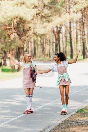 Photo pour Vue pleine longueur de deux amis multiculturels souriants retenant des mains tout en faisant du skateboard sur la route - image libre de droit