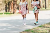 cropped view of two girls holding penny boards while walking on road