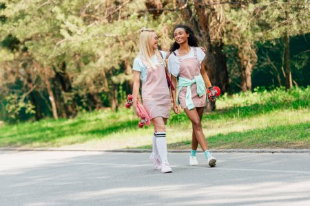 Photo for Full length view of two multicultural friends with penny boards embracing while walking on road - Royalty Free Image