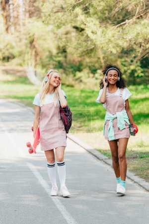 Photo for Full length view of two smiling multicultural friends with penny boards walking on road and listening music in headphones - Royalty Free Image