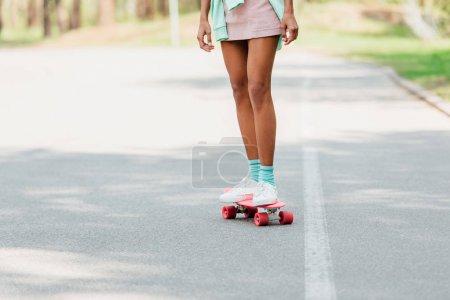 Photo pour Vue partielle de la planche à roulettes américaine africaine de fille sur la route - image libre de droit