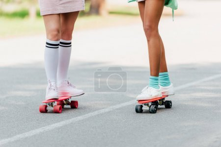Photo for Partial view of two girls skateboarding on penny boards on road - Royalty Free Image