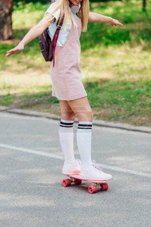 Photo pour Vue partielle de la fille dans des chaussettes de genou faisant du skateboard sur la route - image libre de droit